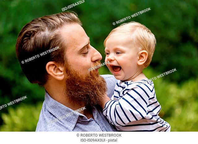 Portrait of father and baby girl, outdoors, laughing