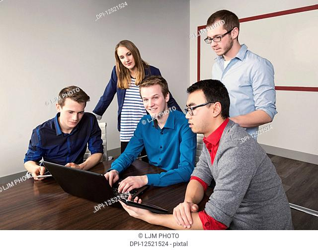 Young millennial business professionals working together in a conference room in a high tech modern business; Sherwood Park, Alberta, Canada