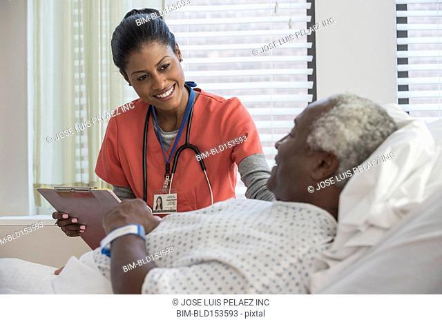 Nurse comforting older man in hospital bed