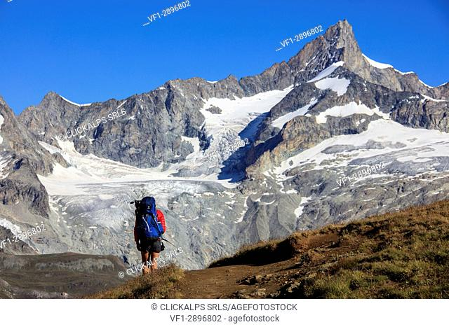 Hiker proceeds on the footpath towards the high peaks in a clear summer day Gornergrat Canton of Valais Switzerland Europe