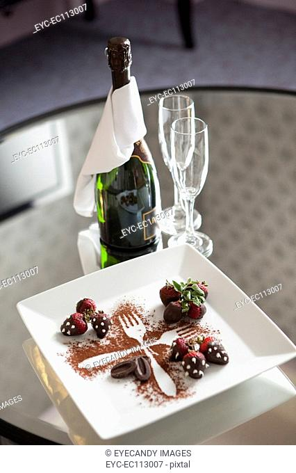 Strawberry desert with champagne bottle and flutes on table