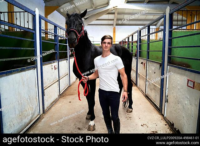 Young man poses with his horse before riding class