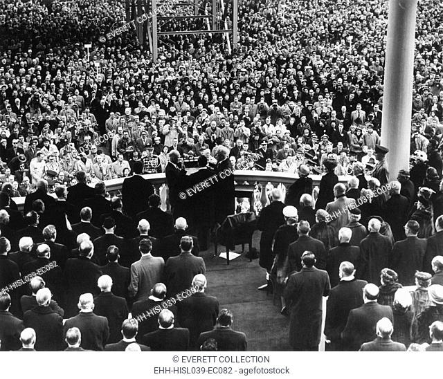 President Eisenhower sworn in by Chief Justice Earl Warren at the public Inauguration. Photo is taken from the back of the Inaugural stage showing the crowd...