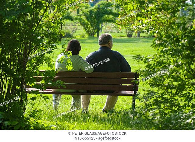 Middle age couple sitting on a bench at a park