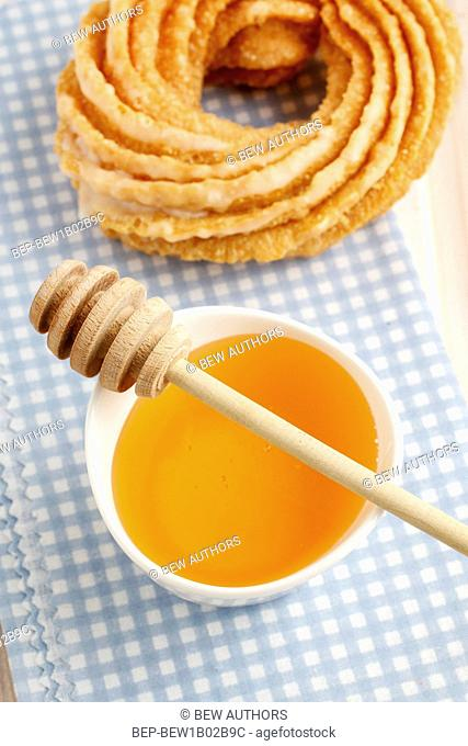 Churro donut and bowl of honey. Party dessert