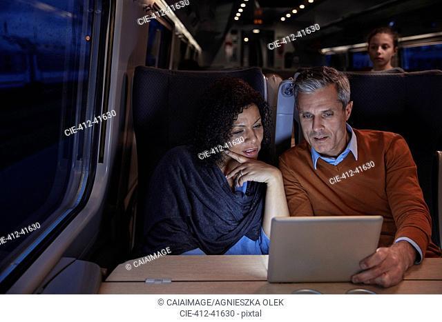 Couple using digital tablet on dark passenger train at night