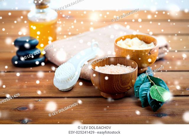 beauty, spa, bodycare, natural cosmetics and concept - himalayan pink salt with massage brush and bath towel on wooden table over snow