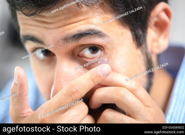 Man putting on contact lens in ophthalmology clinic