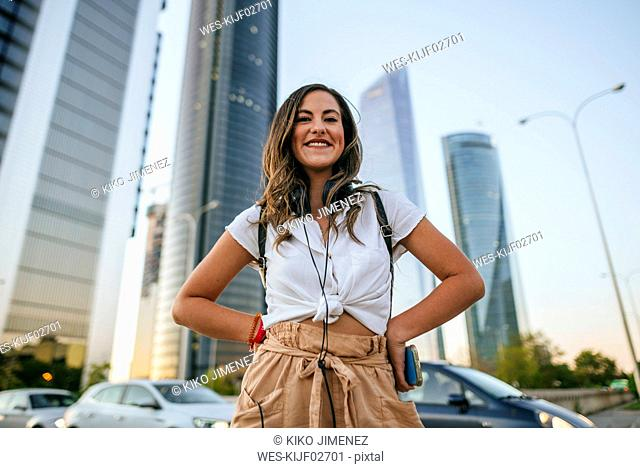 Young woman with headphones on her shoulders, skyscrapers in the background