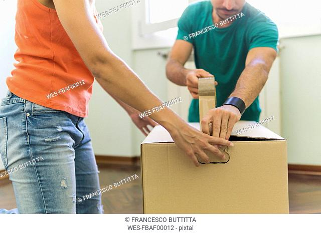 Couple packing cardboard box, partial view