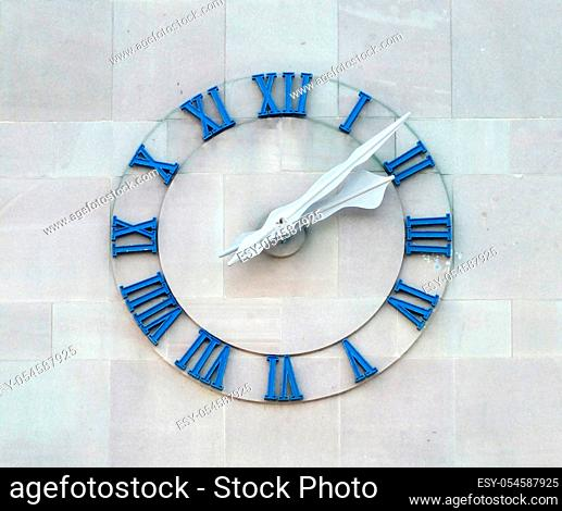 old clock on commercial building wall with roman numerals