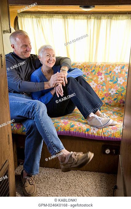 Senior couple sitting on sofa in recreational vehicle, looking away
