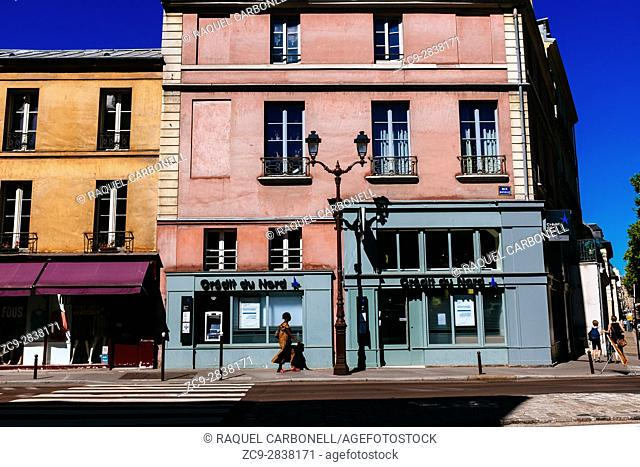 Woman walking down street passing by colourful traditional buildings. Versailles, Île-de-France, France