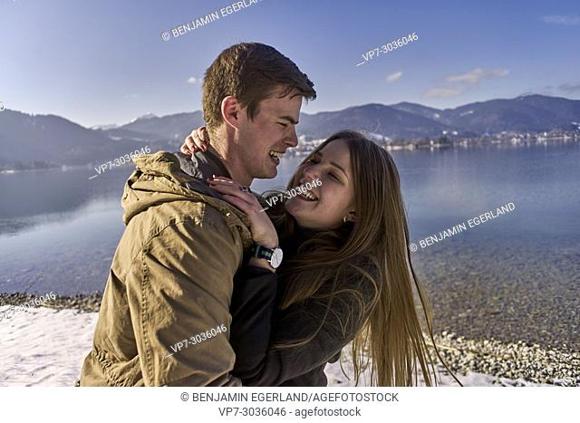 happy couple playing together outside at lake Tegernsee. German ethnicity. Winter time. In Tegernsee, Germany