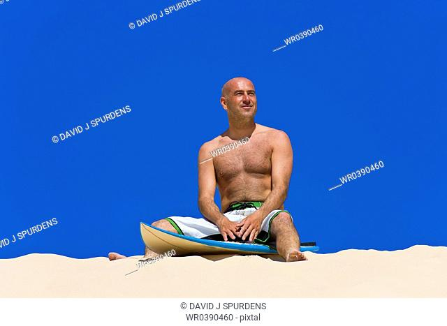Surfer smiles on board sitting on beach