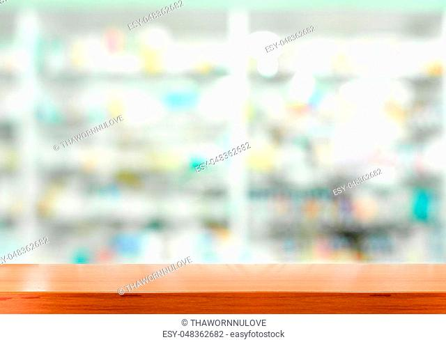 Brown wooden tabletop with blurred pharmacy or medicine shelf at the hospital