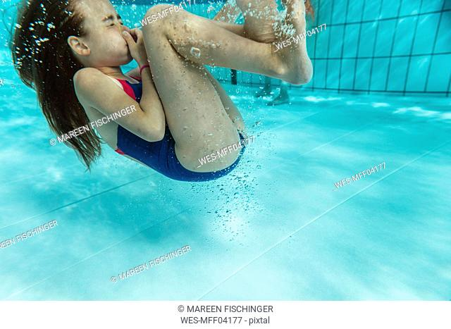 Girl doing a roll under water in swimming pool