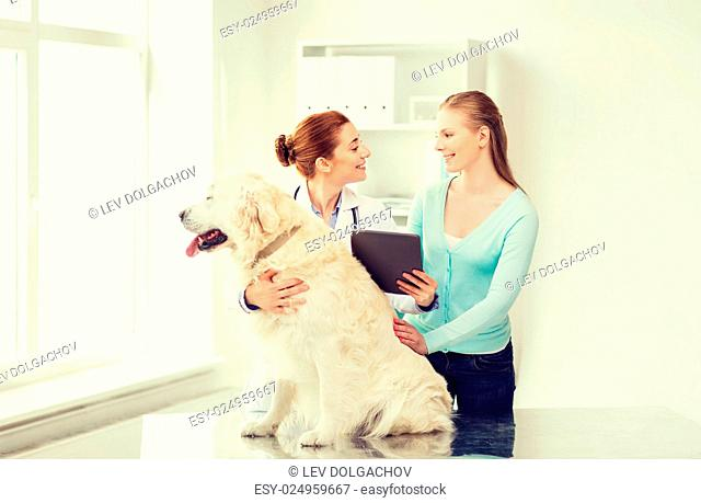 medicine, pet, health care, technology and people concept - happy woman with golden retriever dog and veterinarian doctor holding tablet pc computer at vet...