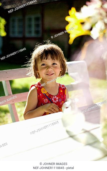 Little girl sitting at picnic table