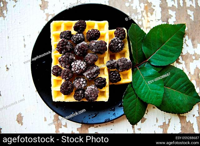 Belgian waffles with blackberries on a wooden background with green leaves