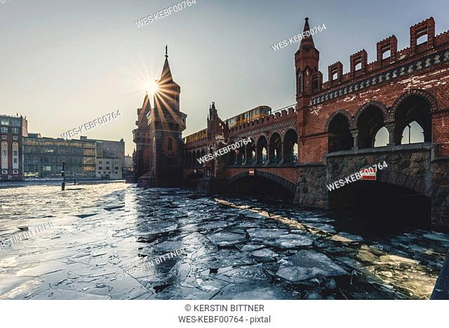Germany, Berlin, view to Oberbaum Bridge with driving underground train in winter