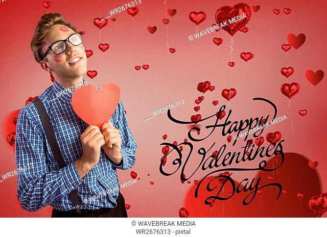 Composite image of valentines text and man holding a red heart