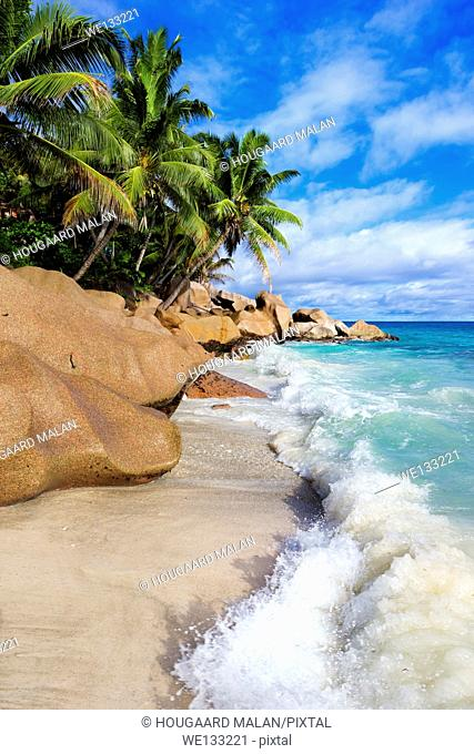 Landscape view of a wave breaking on a tropical beach. La Digue Island, Seychelles
