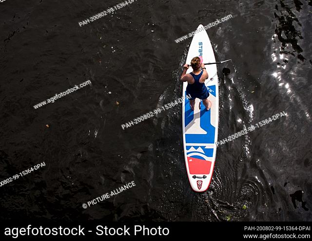 02 August 2020, Hamburg: A woman rides a stand-up paddleboard (SUP) along a canal on the Alster. Photo: Daniel Bockwoldt/dpa
