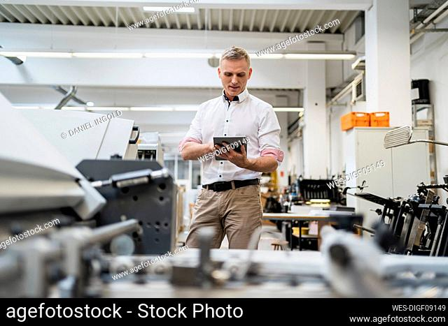 Businessman using a tablet in a factory