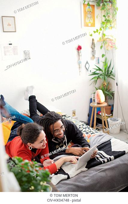 Young couple relaxing, using digital tablet on bed