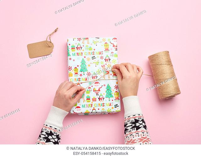 two female hands are wrapping a gift in holiday paper on a pink background, top view, do-it-yourself crafts, festive backdrop