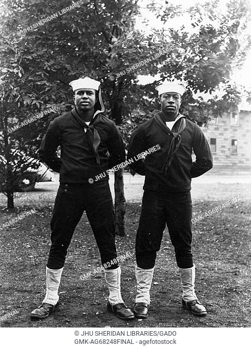 Portrait of two African American US Navy Sailors standing in front of a tree, they are both wearing dark colored sailor uniforms and light colored sailor hats