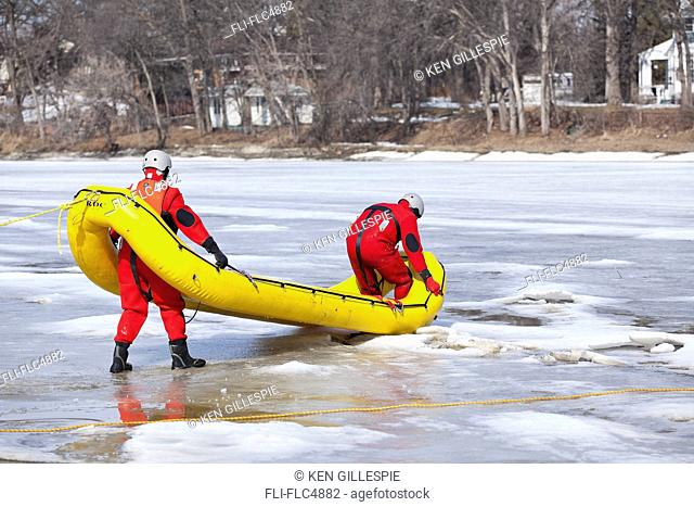 Search and rescue workers, wearing cold water survival gear on the Assiniboine River. Winnipeg, Manitoba, Canada