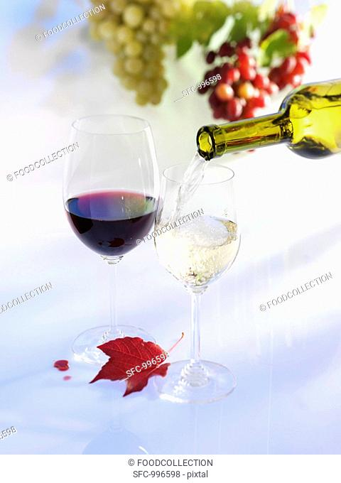 Pouring white wine into glass, glass of red wine, grapes, autumn leaf