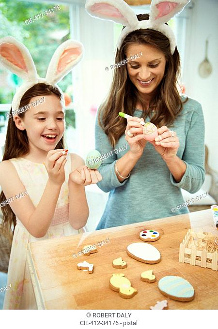 Mother and daughter wearing costume rabbit ears decorating Easter eggs