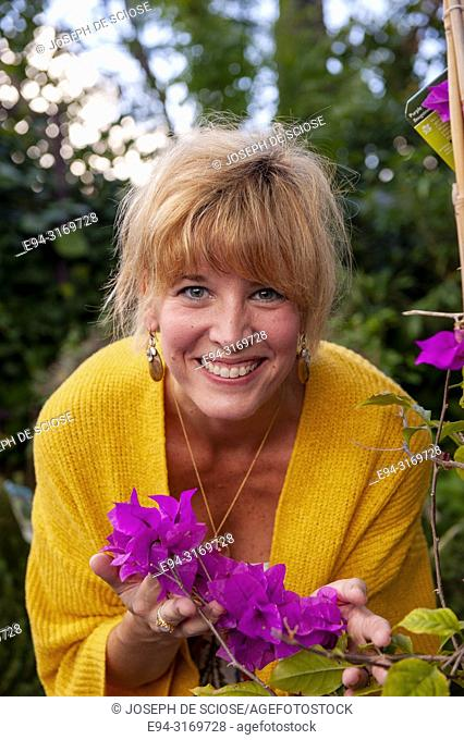A pretty 42 year old blond woman smiling at the camera holding flowers of a Bougainvillea plant