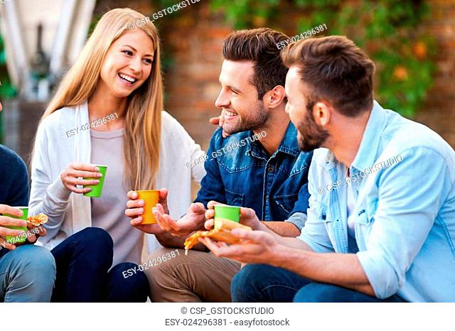 Quality time with best friends. Group of happy young people talking to each other and eating pizza while sitting outdoors