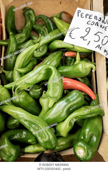Heap of green pepperoni chilli peppers for sale at market, Puglia, Italy