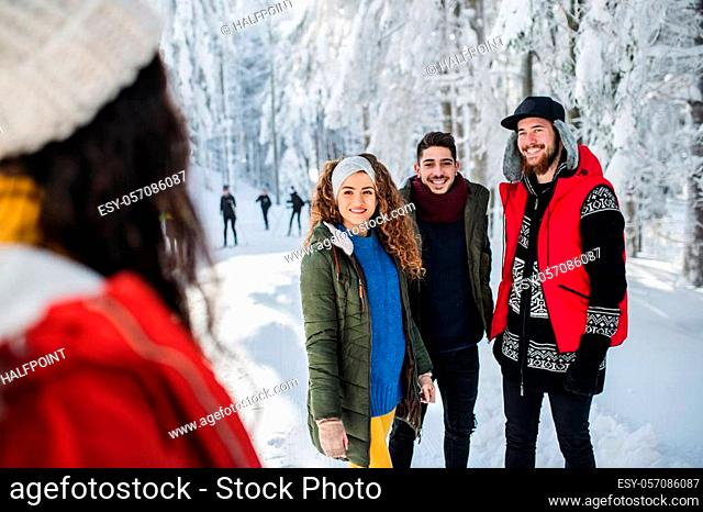 A group of young cheerful friends on a walk outdoors in snow in winter, talking
