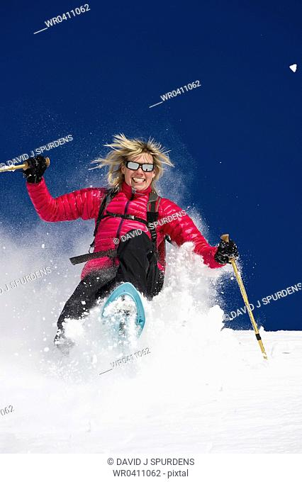 A woman having fun snowshoeing through deep fresh powder snow