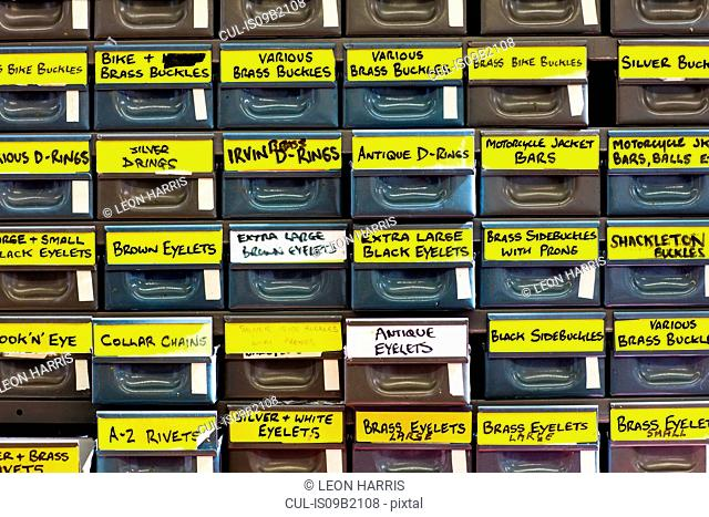 Labelled drawers of textile parts in leather jacket manufacturers, close-up