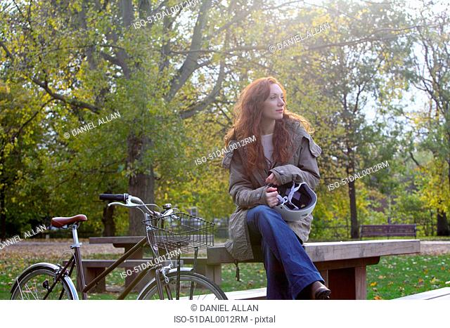 Woman sitting with bicycle in park