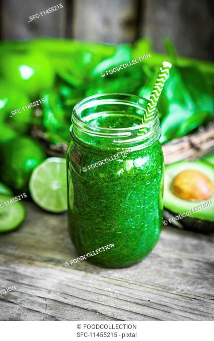 A green smoothie on a rustic wooden surface