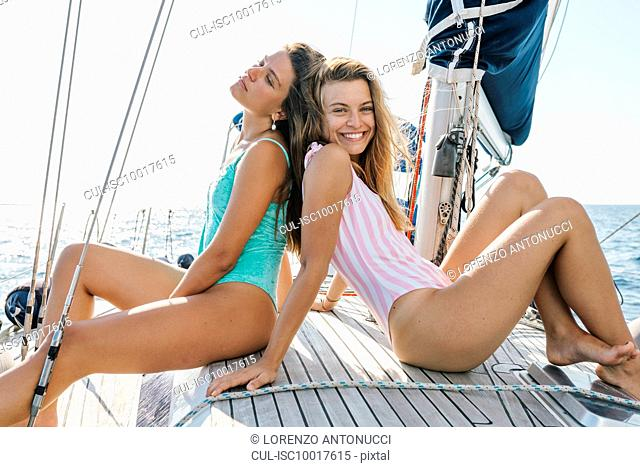 Friends sunbathing on deck of sailboat, Italy