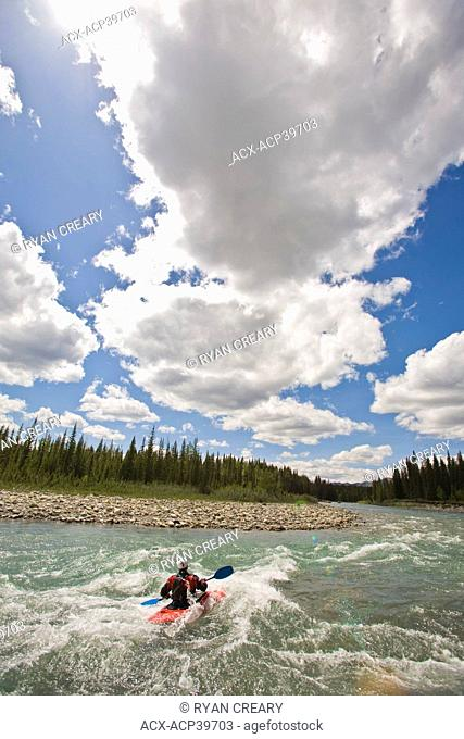 A middle aged man surfs the rapids in his kayak on the Red Deer River, Alberta, Canada