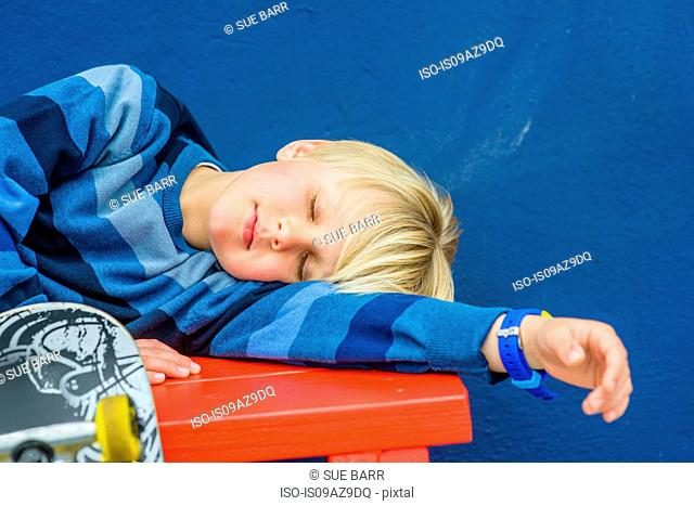 Boy with skateboard asleep on red bench