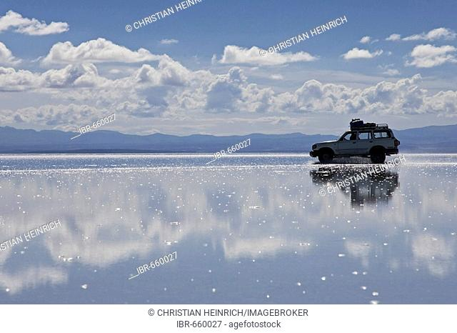 Driving car on the salt lake Salar de Uyuni, Altiplano, Bolivia, South America