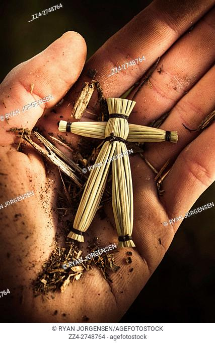 Man holding a small straw or wooden voodoo doll and dirt in his palm in a concept of cult ritual and magic based on an animist religion from Africa and the...