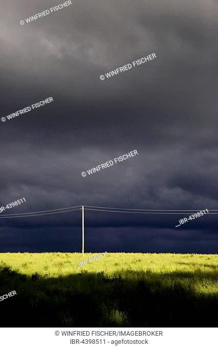 Dark cloudy sky on the horizon, power line and power pole