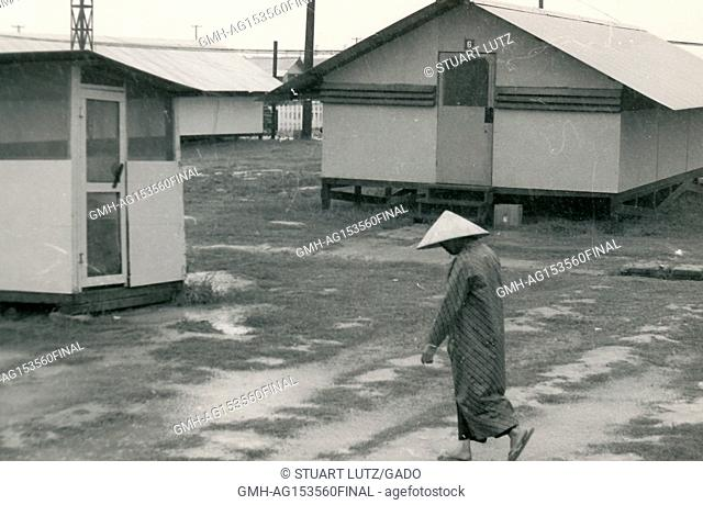 A Vietnamese woman wearing a traditional hat walks through an American barracks during the Vietnam War, 1968. ()